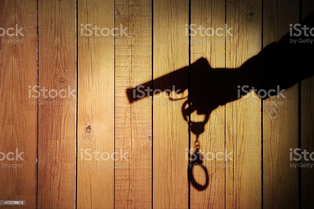 Male Hand with Gun and Handcuffs on Natural Wood Background royalty-free stock photo