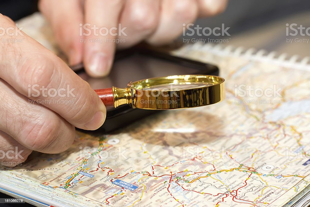 male hand with magnifying glass over a map royalty-free stock photo