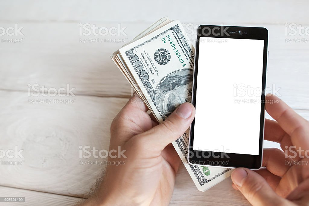 Male hand with smartphone and american cash, mokup stock photo
