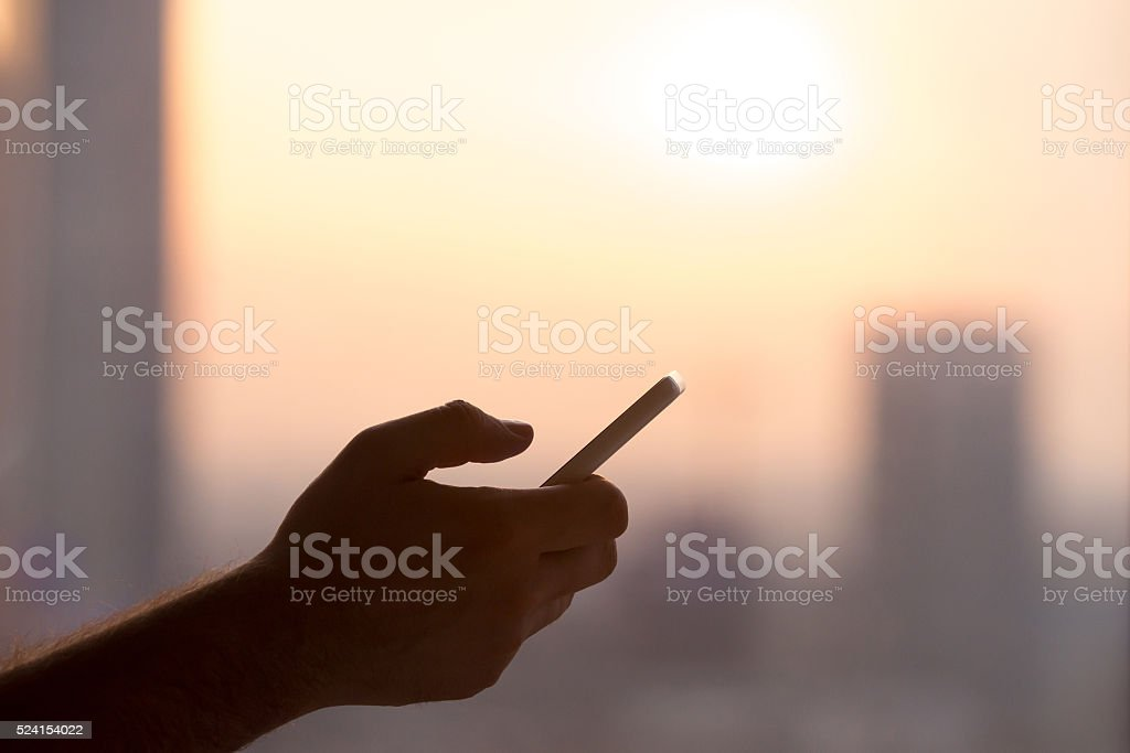 Male hand with smartphone at sunset stock photo