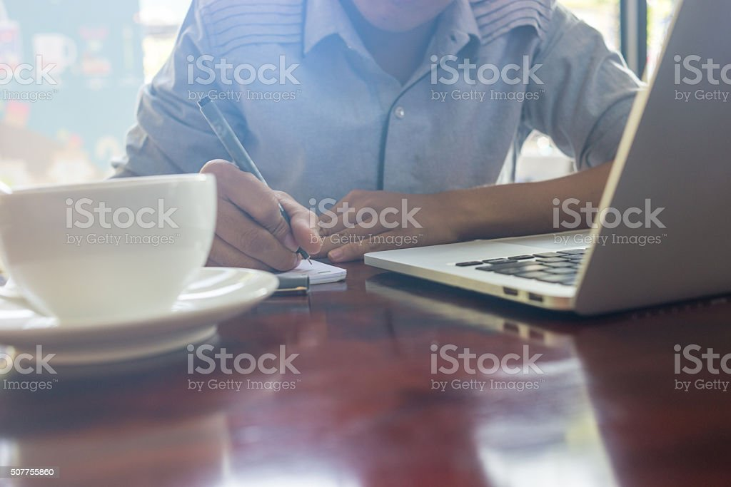 Male hand writing notes with laptop and coffee beside stock photo