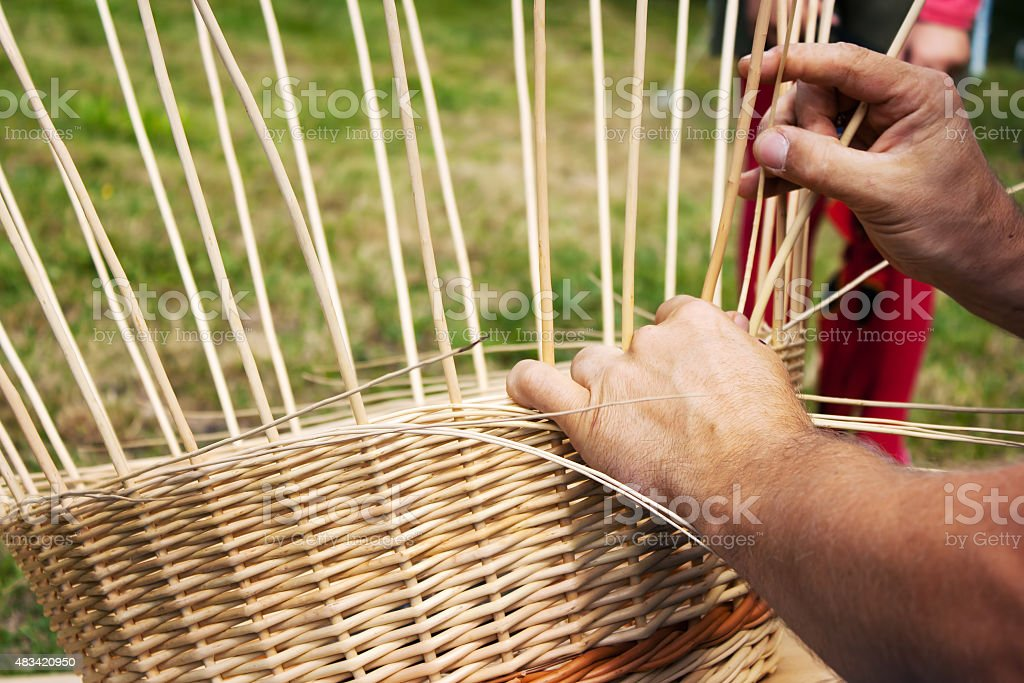 male hands braiding wicker basket stock photo