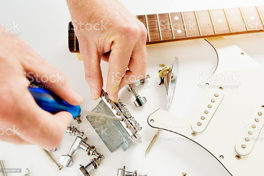 Male hands busy fixing disassembled electric guitar stock photo
