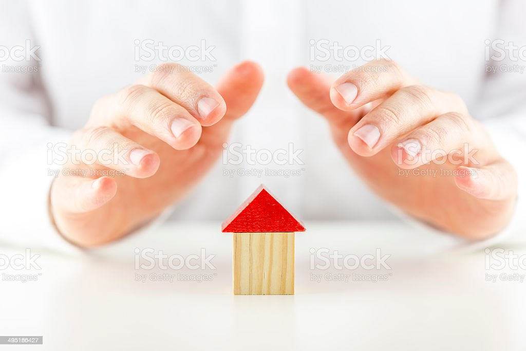 Male hands covering and protecting a home stock photo