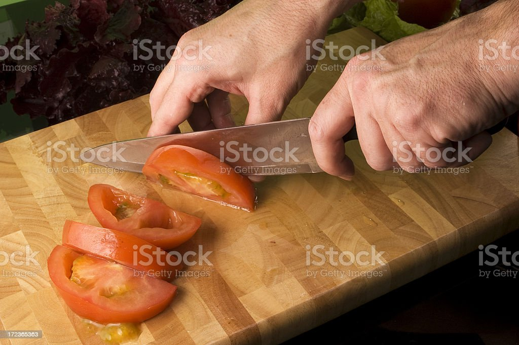 Male hands cutting tomatoes royalty-free stock photo