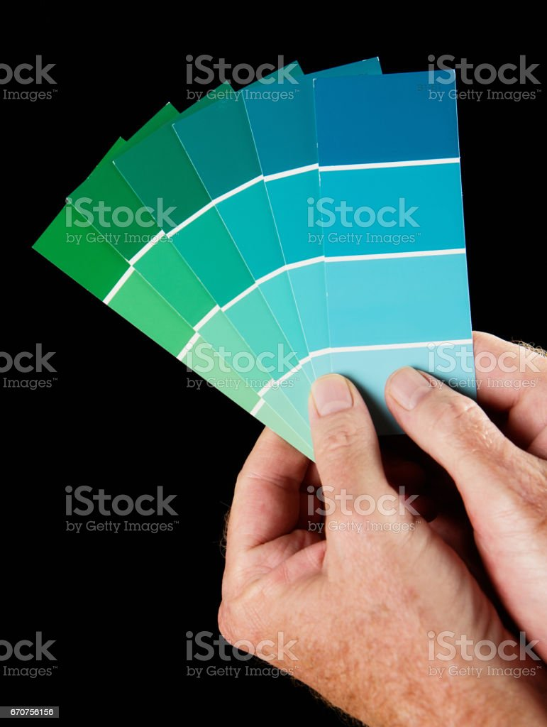 Male hands hold fanned-out blue and green coloured paint swatches stock photo