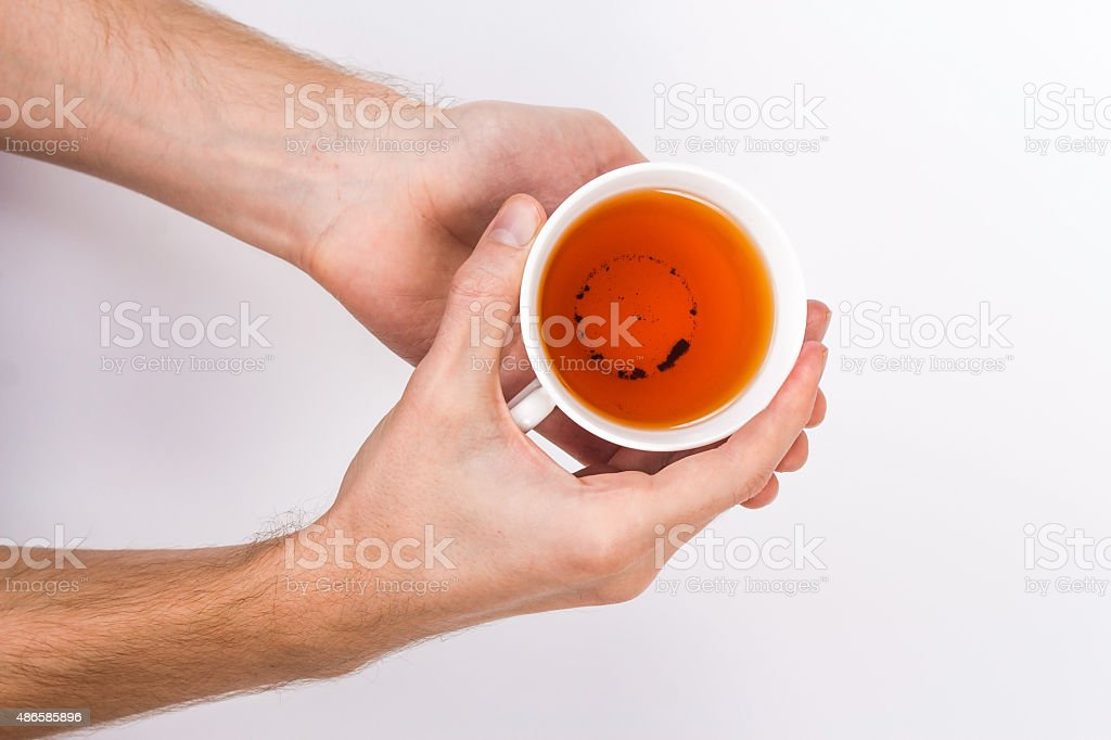 male hands holding a cup of tea. stock photo