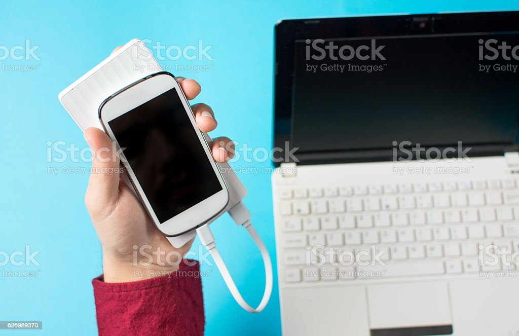 male hands holding a white cellphone connected to a power stock photo