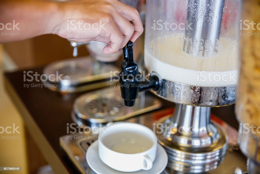 Male hands holding faucet milk dispenser stock photo