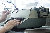 Male hands holding glasses and typing on typewriter