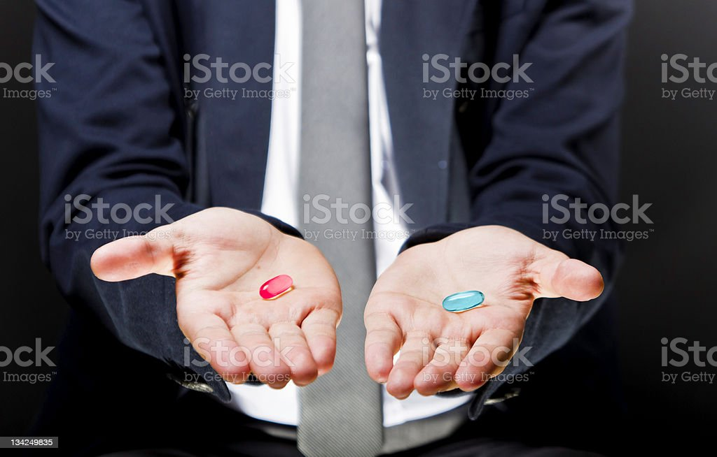 Male hands holding two gel pills One is red the other blue stock photo