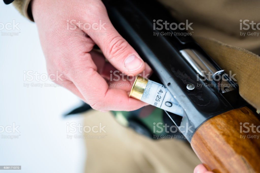 male hands hunter inserted cartridge rifle on a backg stock photo