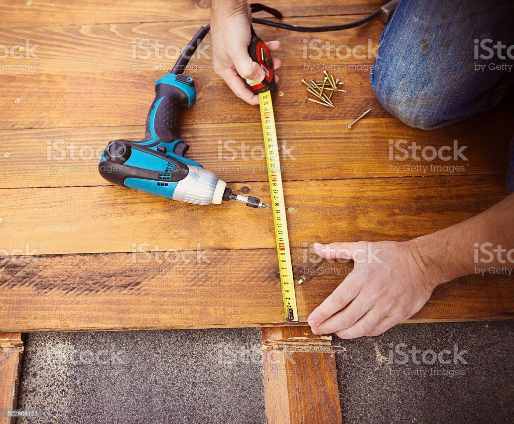 Male hands measuring wooden floor stock photo