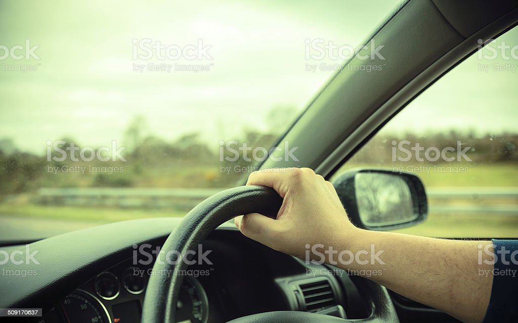 Male hands on steering wheel of a car and road stock photo
