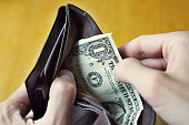 Male hands opening almost empty leather wallet with one Dollar