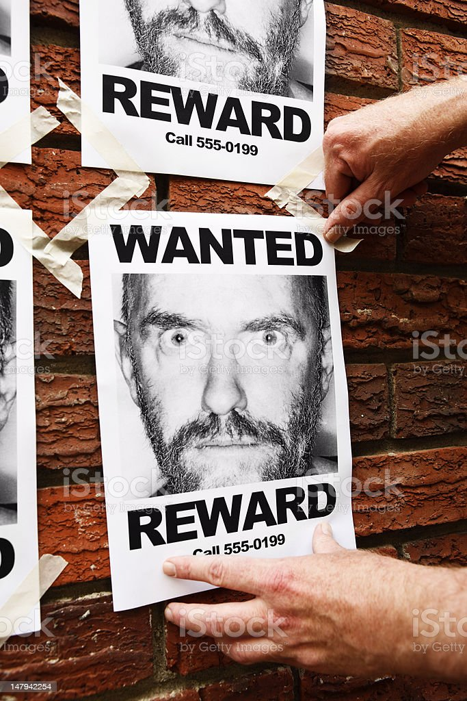 """Male hands pin """"Wanted"""" poster to brick wall. royalty-free stock photo"""