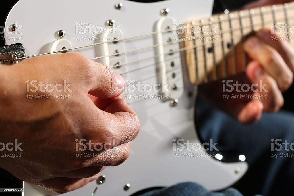 Male hands playing electric guitar with plectrum closeup stock photo