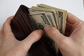 Male hands pulling a Dollar bank notes from wallet