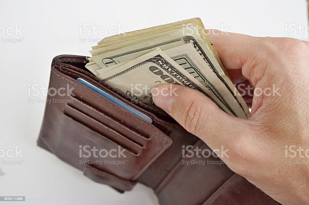 Male hands pulling a Dollar bank notes from wallet stock photo