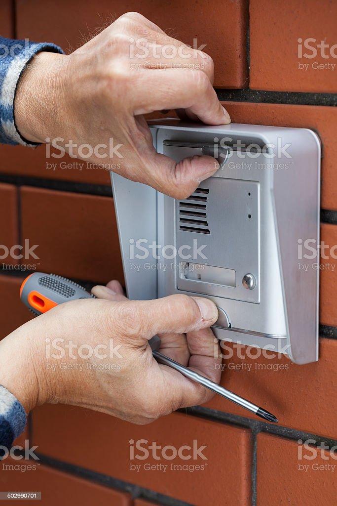 Male hands repairing intercom stock photo