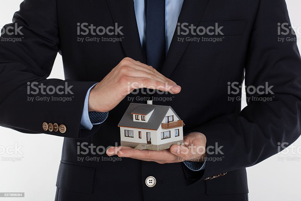 Male hands saving small house with a roof. stock photo
