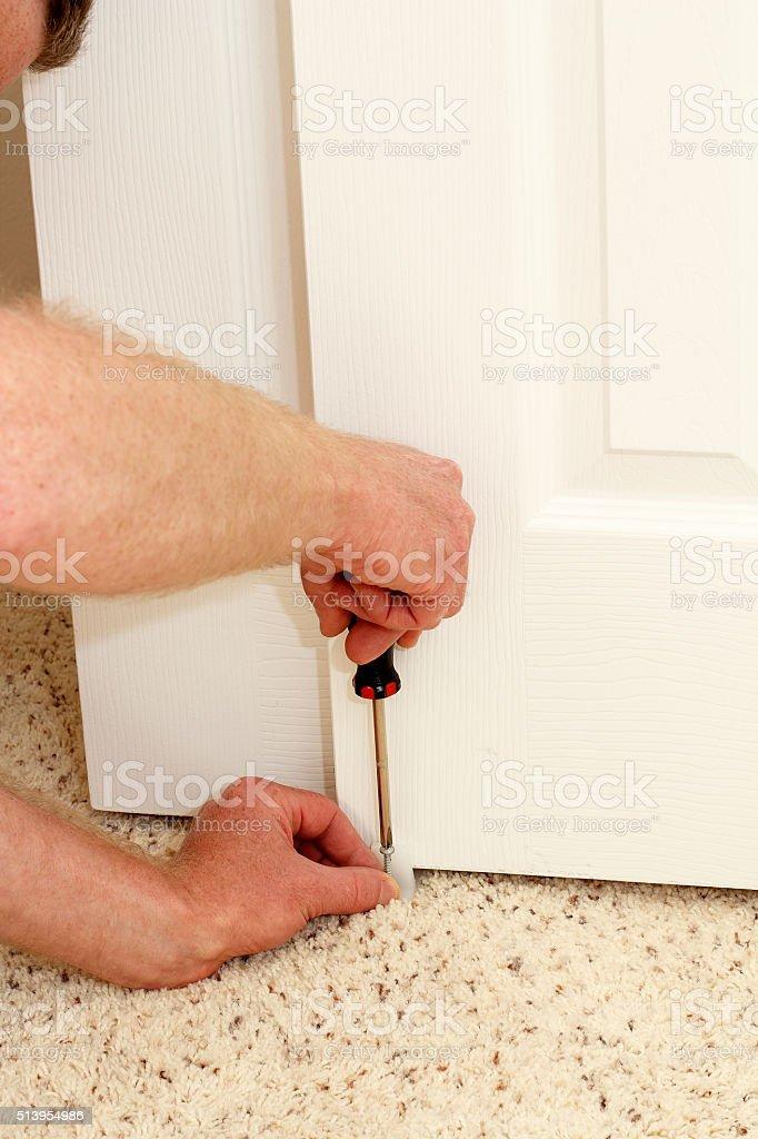 Male Hands Screwing in a Door Guide stock photo
