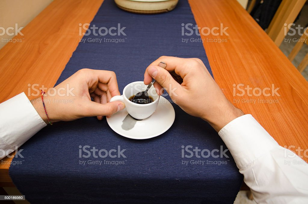 Male hands stirring espresso coffee in a cup stock photo