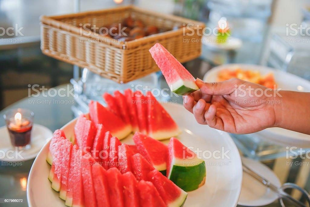Male hands taking watermelon at breakfast buffet stock photo