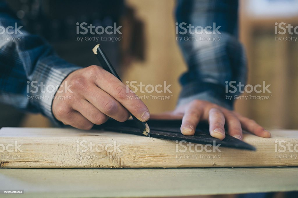 Male hands using a square and a pencil to mark 2x4 stock photo