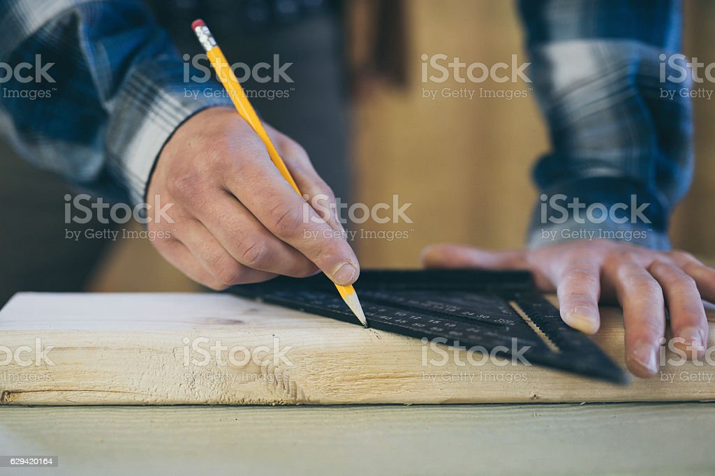 Male hands using a square and pencil to mark 2x4 stock photo