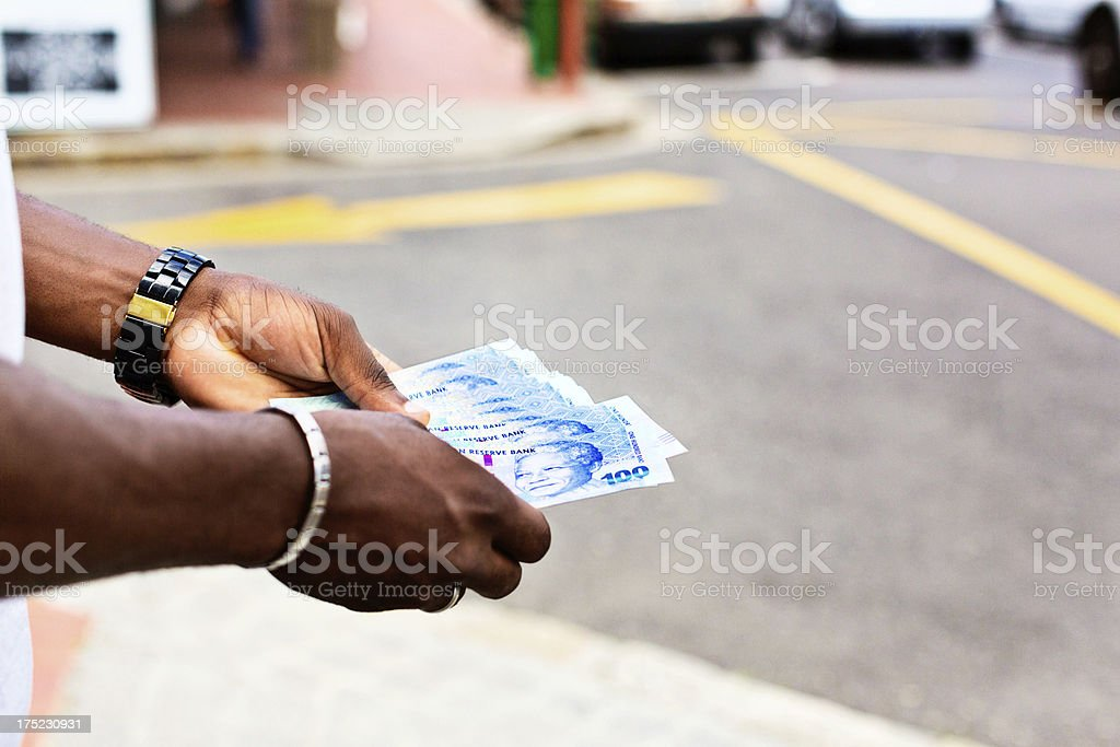 Male hands with Hundred Rand banknotes on street corner royalty-free stock photo