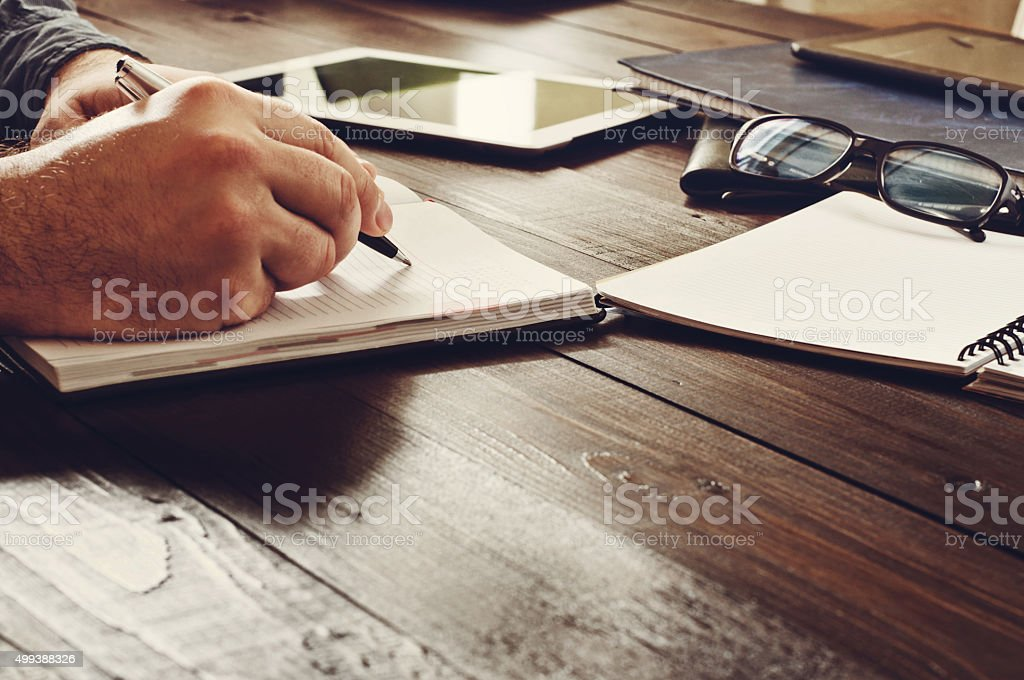 Male hands writing in a notebook stock photo