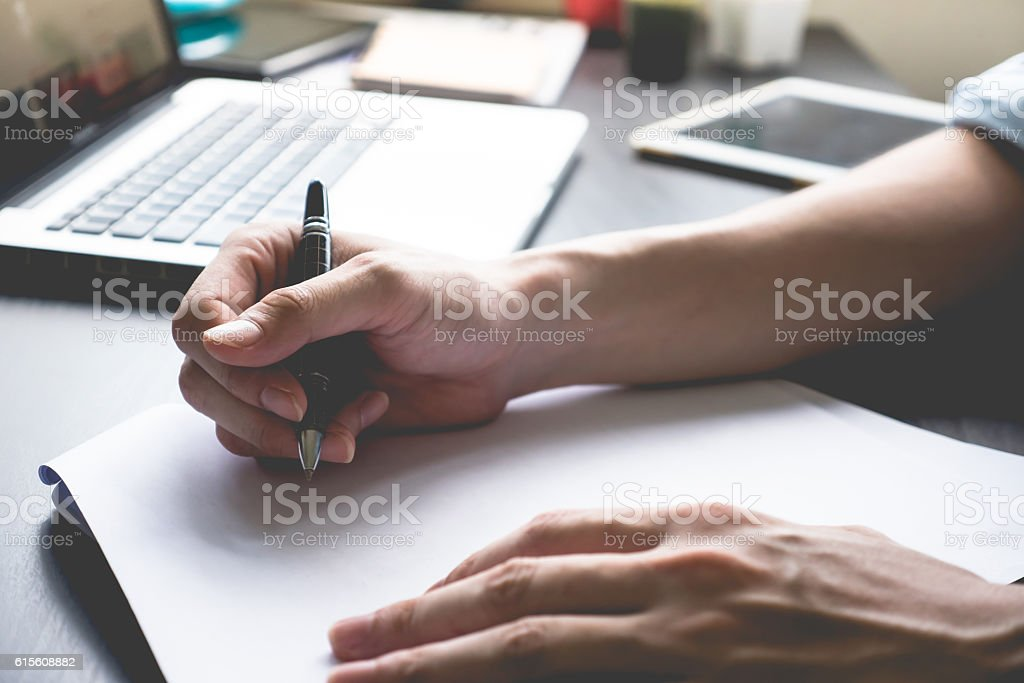 male hands writing on paper on his desk. stock photo