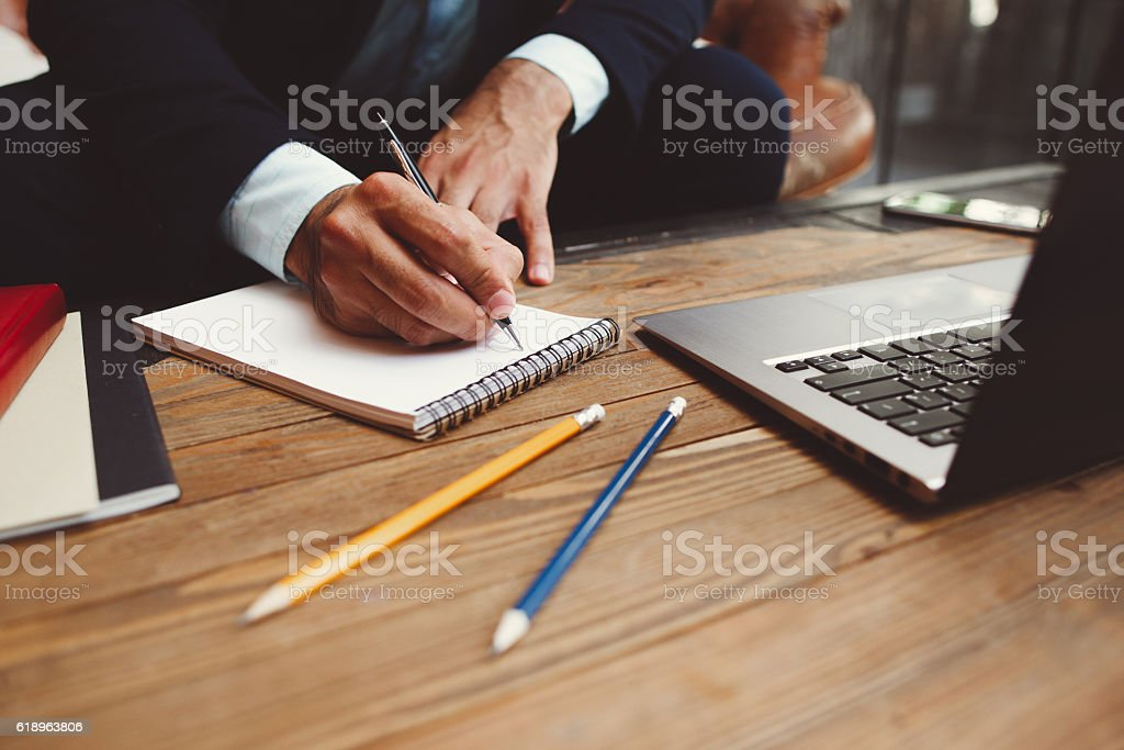 Male hands writing plans in notepad stock photo