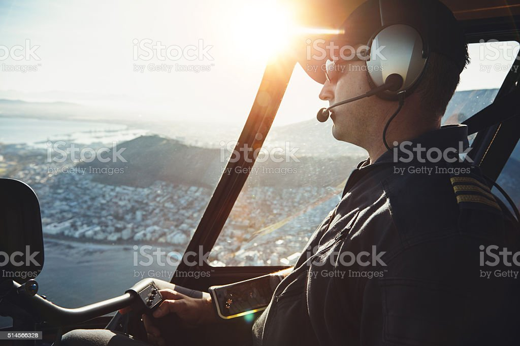 Male helicopter pilot flying aircraft stock photo