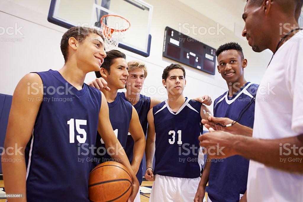 Male High School Basketball Team Having Team Talk With Coach stock photo