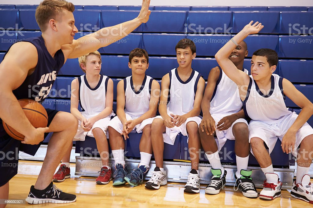 Male High School Basketball Team Having Team Talk With Coach stock photo