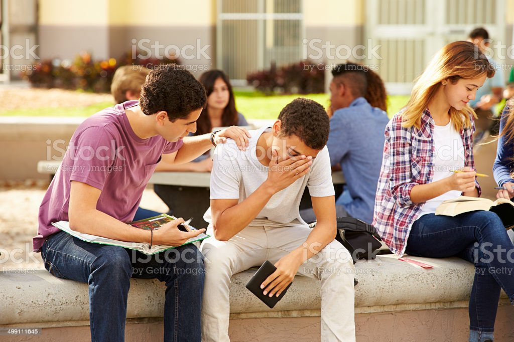Male High School Student Comforting Unhappy Friend stock photo