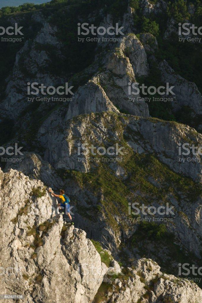 Male hiker climbing on steep rock ridge  outdoors in nature stock photo