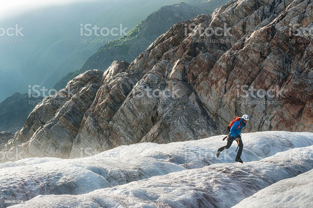 Male hiker jumps across an icy crevasse stock photo