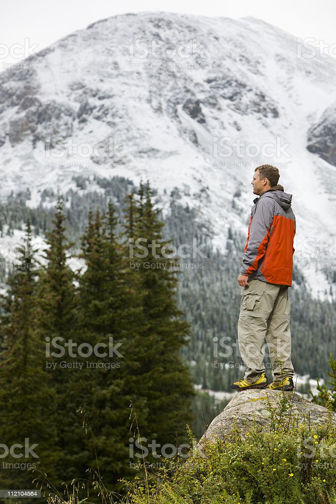 Male hiker on rock with mountain backdrop. royalty-free stock photo