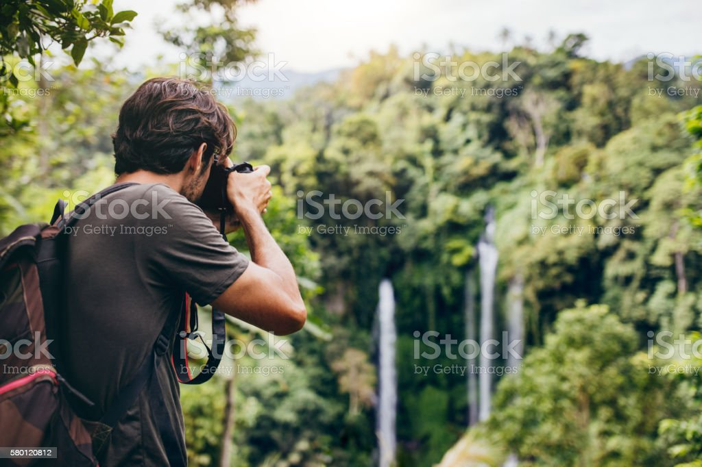 Male hiker photographing a waterfall in forest stock photo
