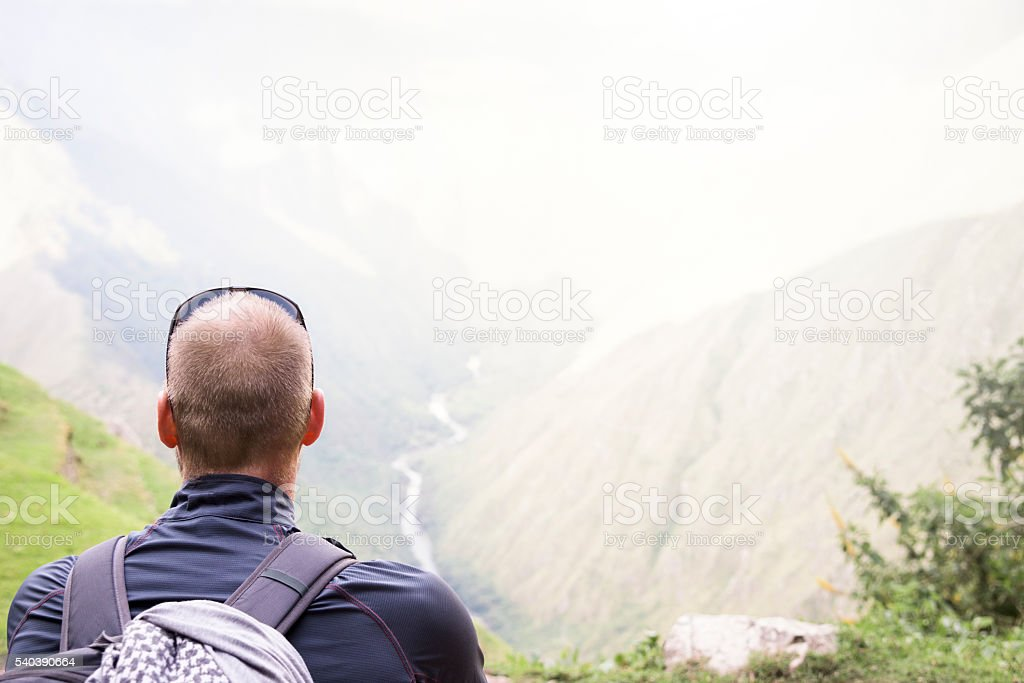 Male hiker sitting looking out over mountains and valleys stock photo
