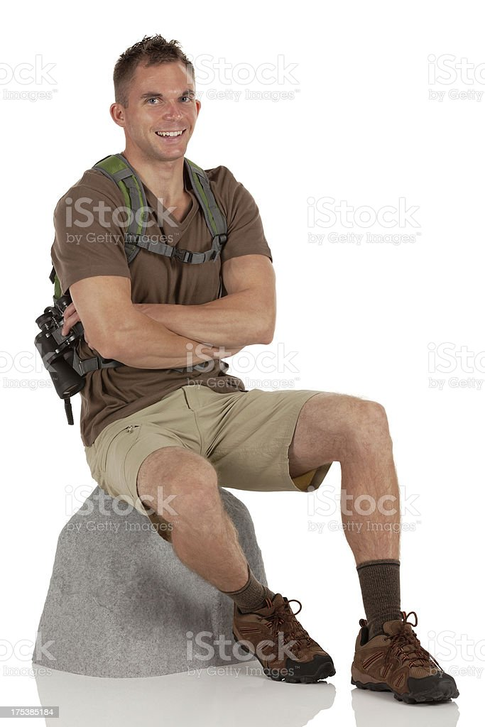Male hiker sitting on a boulder stock photo