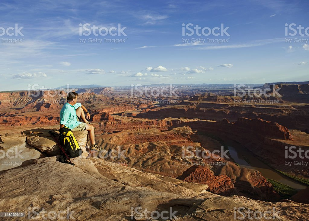 Male Hiker Sitting On Rocks Looking Out Over Canyonlands stock photo
