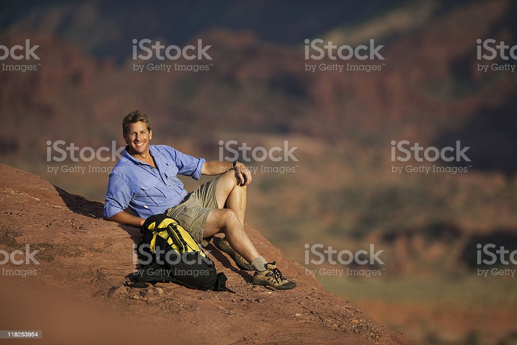 Male Hiker Sitting On Rocky Ledge With Backpack royalty-free stock photo