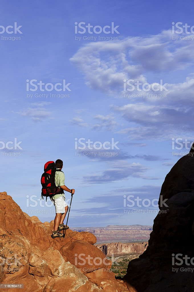 Male Hiker Standing On Rocky Ledge Looking At Spectacular View royalty-free stock photo