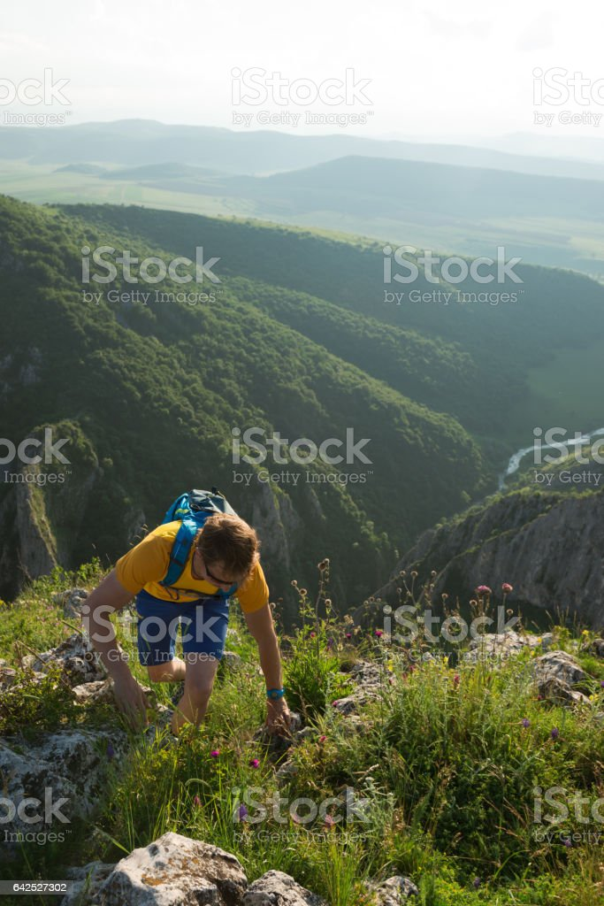 Male hiker walking uphill on a summer day stock photo
