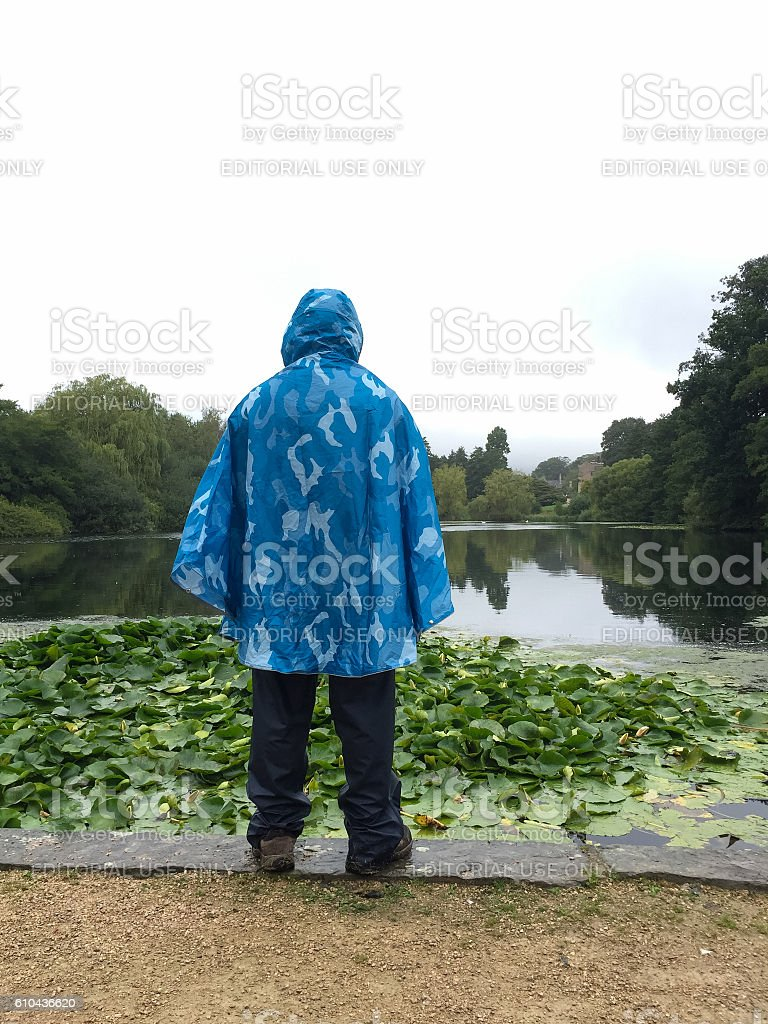 Male hiker wearing waterproof poncho and trousers, Newstead Abbe stock photo