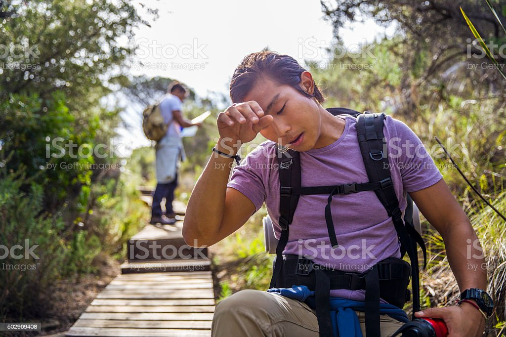 Male hiker wiping sweat from forehead stock photo